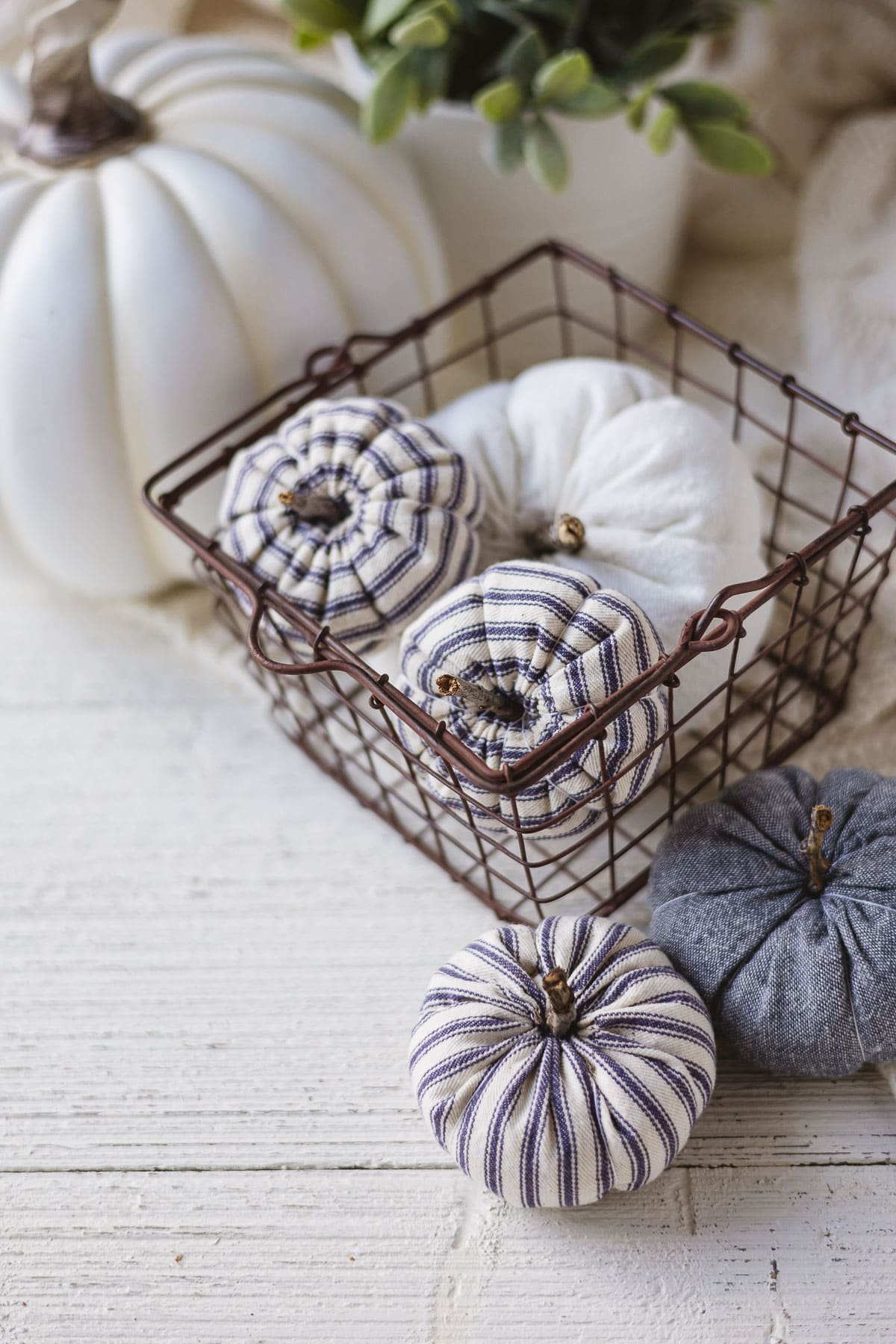 Ticking stripe and blue linen handmade pumpkins in a wire basket on a wooden surface.