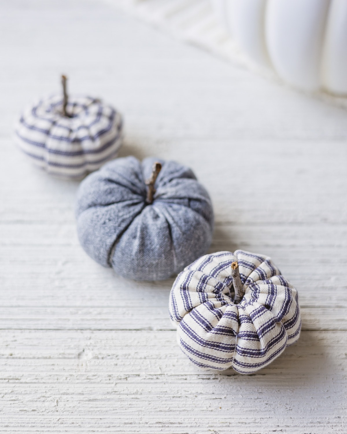 Ticking stripe and linen pumpkins on a white wooden surface.