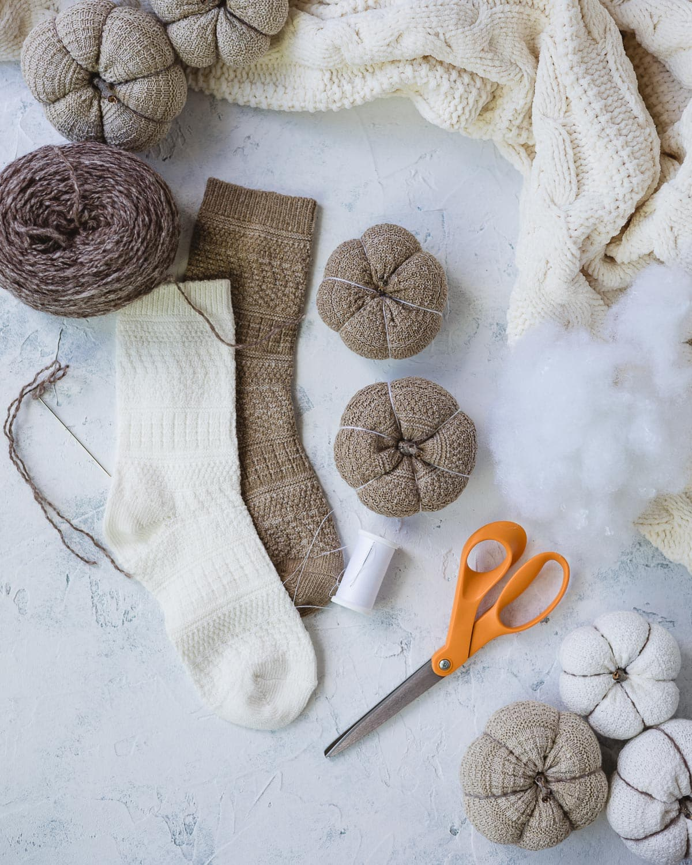 Socks, sock pumpkins, orange scissors, and a needle and thread.