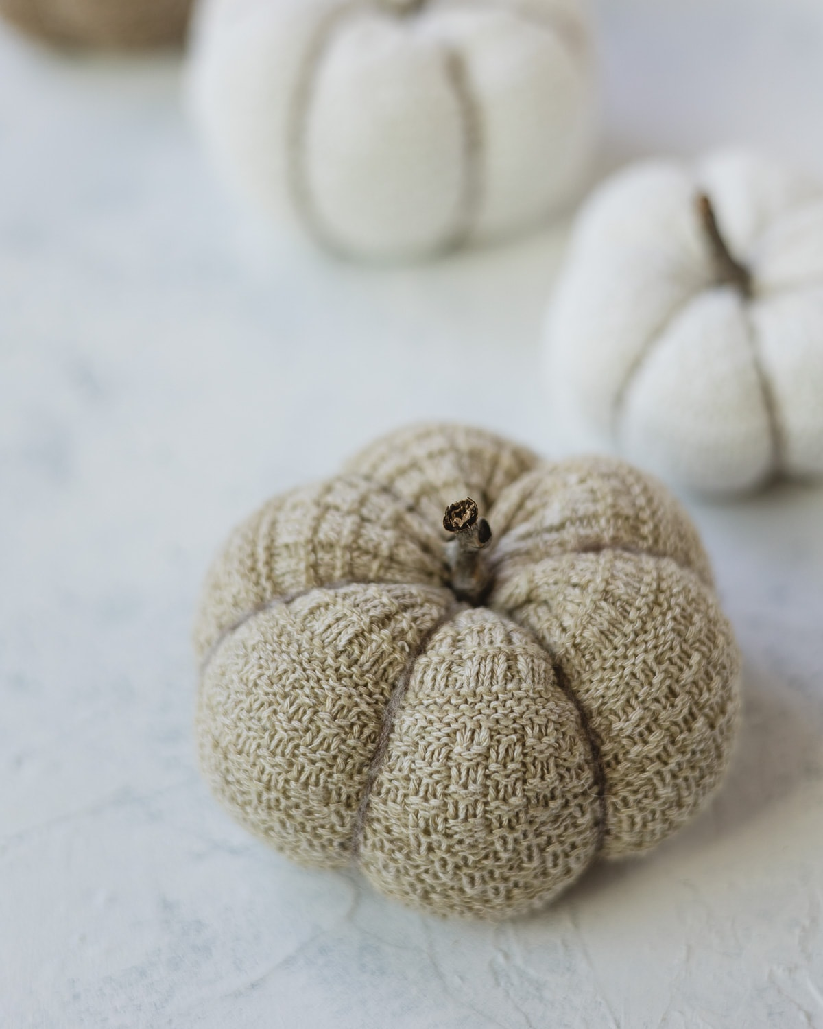 A brown knit pumpkin made from a sock with a twig stem.