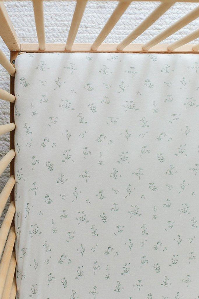 A floral crib sheet on a mattress inside a wooden crib.