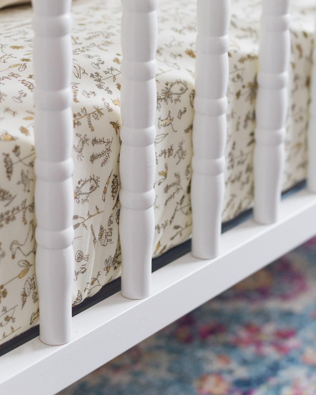 A white Jenny Lind Crib with a crib mattress inside.