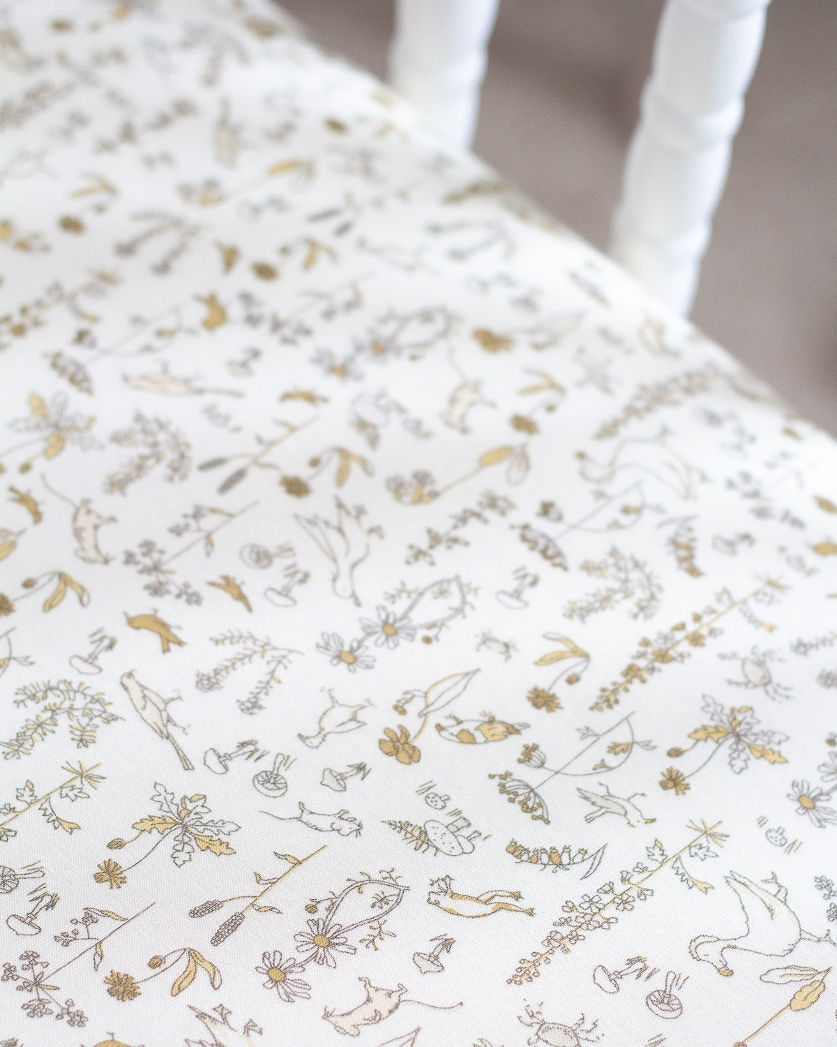 A close up view of a woodland animal patterned crib sheet.