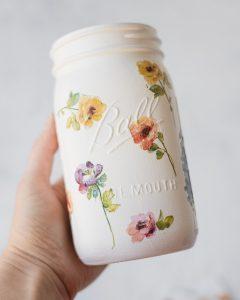 Holding a DIY floral mason jar vase.