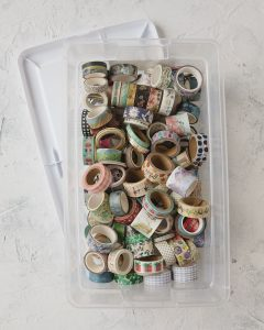 A clear storage box filled with washi tape.