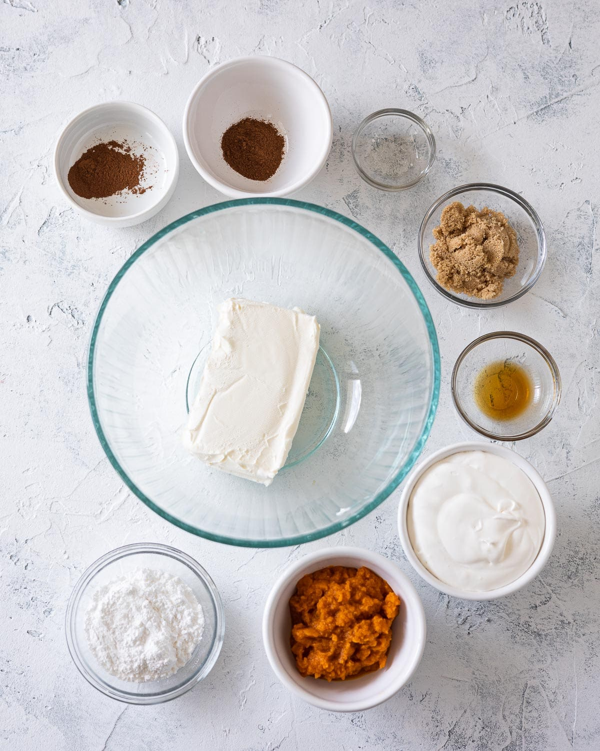 Ingredients for no bake pumpkin cheesecake in glass bowls: spices, sugars, cream cheese, pumpkin, whipped topping, salt, and vanilla.