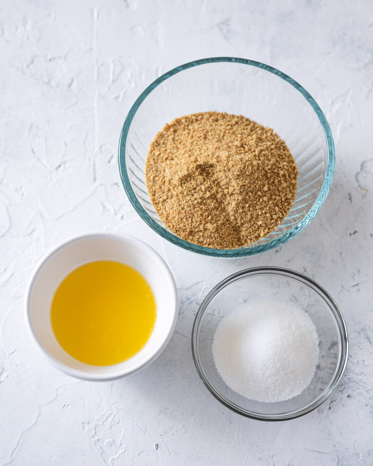 Three ingredients for graham cracker crust: graham cracker crumbs, melted butter, granulated sugar.