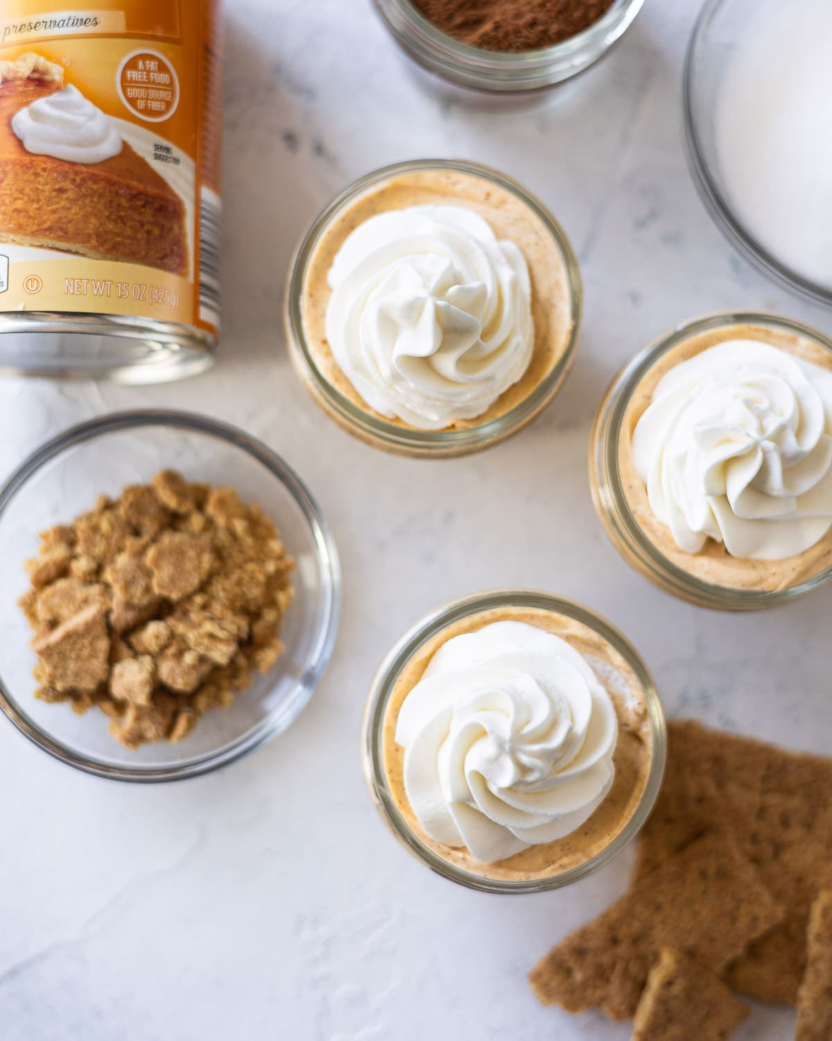 Mini mason jar pumpkin cheesecakes topped with rosettes of whipped cream.