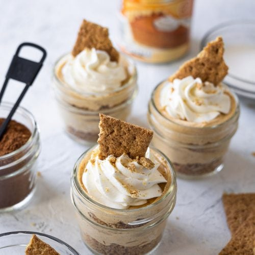 Mini pumpkin cheesecakes topped with whipped cream and graham cracker shards.
