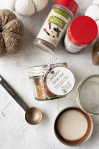 A jar of homemade pumpkin spice mix tied with a printable gift tag.
