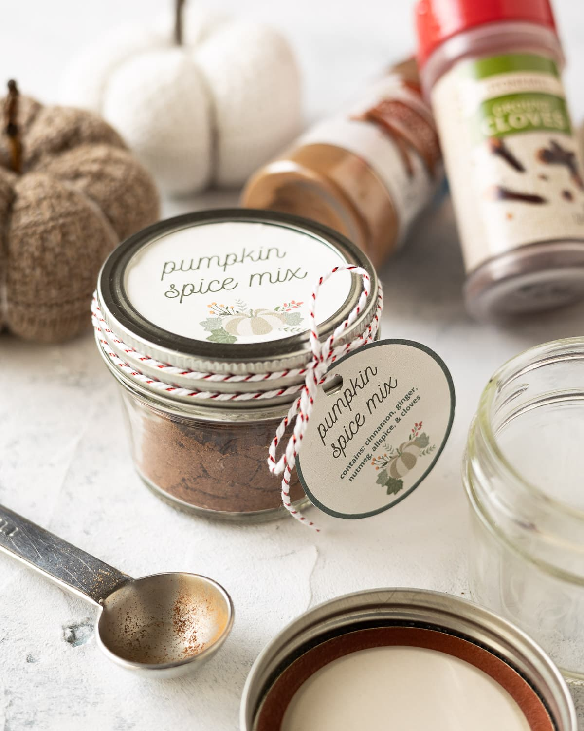 A jar of homemade pumpkin spice mix surrounded by spice jars and a measuring spoon.