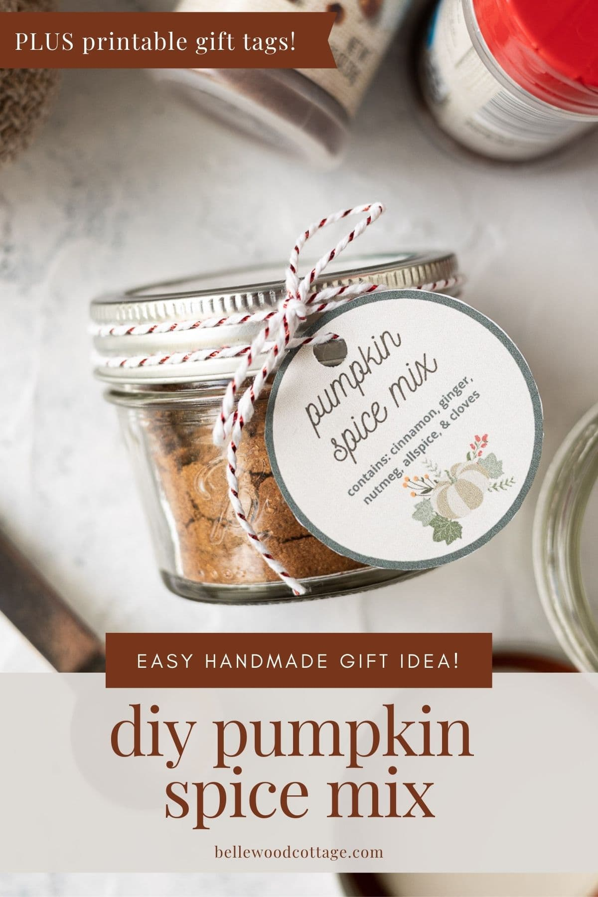 """A small mason jar filled with pumpkin spice mix and and tied with a gift tag, with the words, """"DIY Pumpkin Spice Mix - Easy Handmade Gift Idea, Plus Printable Gift Tags""""."""